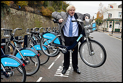 The London Mayor Boris Johnson with lifts up a Barclays Bike as he expands the Barclays Cycle Hire to Wandsworth, South West London, United Kingdom. Friday, 13th December 2013. Picture by Andrew Parsons / i-Images