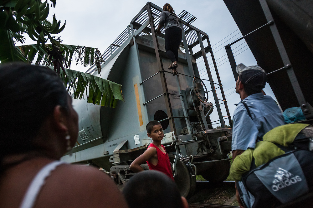 """TENOSIQUE, MEXICO - MAY 29, 2014: Migrant families climb on top of """"The Beast"""" a train that goes from southern Mexico to just south of the Texas border.  Migrants have ridden on top of its train cars for years during their journey north.  In recent months, authorities have noted a boom in child migrants arriving in the United States. PHOTO: Meridith Kohut for The New York Times"""