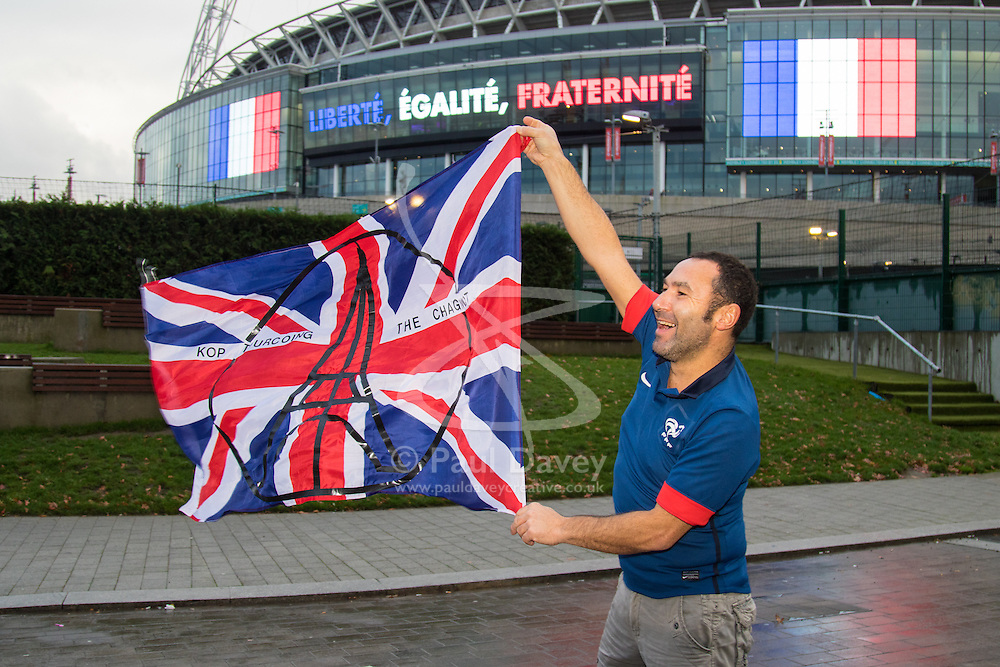 Wembley Stadium, London, November 17th 2015. Hours befor kick-off French and England fans begin to gather outside Wembley Stadium as both England and France national teams are poised to play in an emotional tie just days after the tragic death of 130 people in the Paris Islamist attacks. PICTURED: A French fan's flag blows in the breeze outside the stadium. // Licencing Contact: paul@pauldaveycreative.co.uk Mobile 07966 016 296