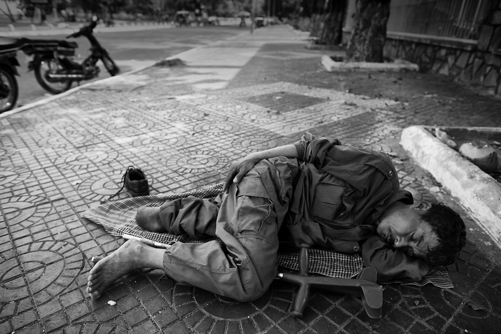A landmine victim sleeps on a Phnom Penh, street.