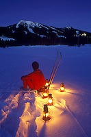 A cross country skier takes a break during a lantern ski in Paradise Meadows up at Mount Washington.  Courtenay, The Comox Valley, Vancouver Island, British Columbia, Canada.