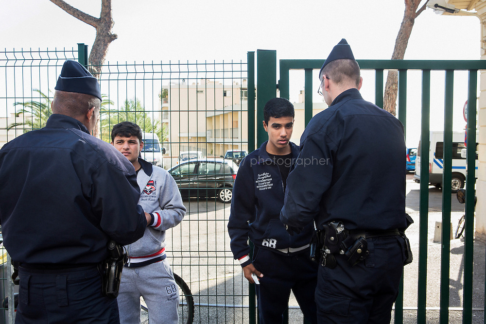 MENTON, FRANCE - 20 NOVEMBER 2014: Two Afghan refugees are questioned by the French police after being caught on the train that goes from Ventimiglia to Nice, taken by migrants that want to cross the border from Italy to France, in Menton, France, on November 20th 2014.<br /> <br /> The Ventimiglia-Menton border is the border between Italy and France crossed by migrants who decide to continue their journey up north towards countries such as Germany, Sweden, The Netherlands and the UK where the process to receive the refugee status or humanitarian protection is smoother and faster. in Ventimiglia, Italy, on November 17th 2014.