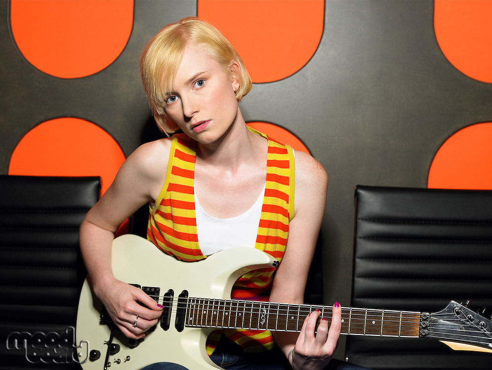 Young woman playing guitar portrait