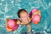 Girl Floating Using Two Pink Rubber Ducks