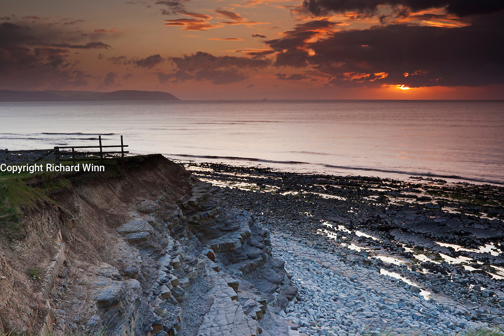 The setting of the sun on a cloudy and showery evening at Kilve Beach, from the cliffs looking out over the Bristol Channel.