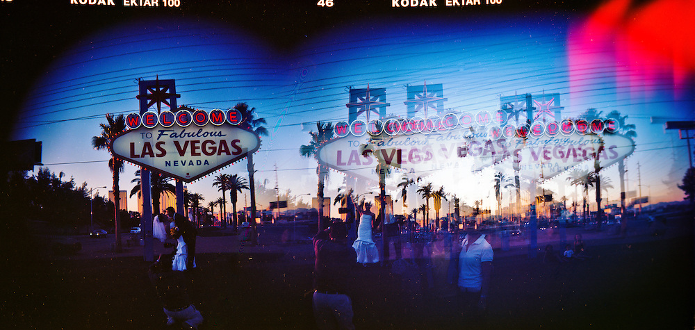 Newlyweds posing in front of the Las Vegas sign.