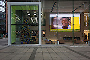 A face smiles out from a screen in the Aviva office foyer during a rolling video for the insurance corporate, on 9th December 2016, in the City of London.