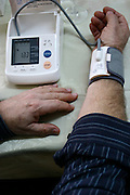 man self testing blood pressure and heart rate with a digital blood pressure monitor .