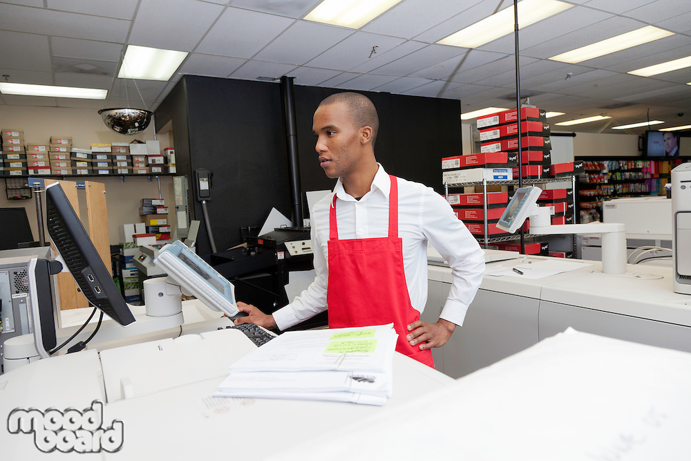 Manual worker looking at cash register machine