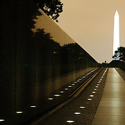 Night shot of the Vietnam Veterans Memorial with the Washington Monument with the orange glow of city lights against low clouds.