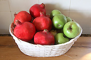 Still life basket of pomegranates and apples as a preparation for the Jewish  Rosh Hashana holiday