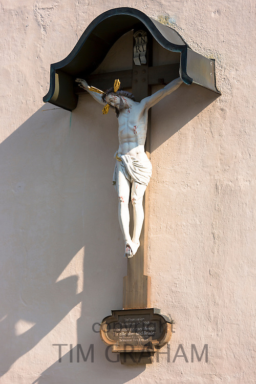 Crucifix of Jesus Christ  on the wall of the Church of St Peter and Paul in Oberammergau in Upper Bavaria, Germany