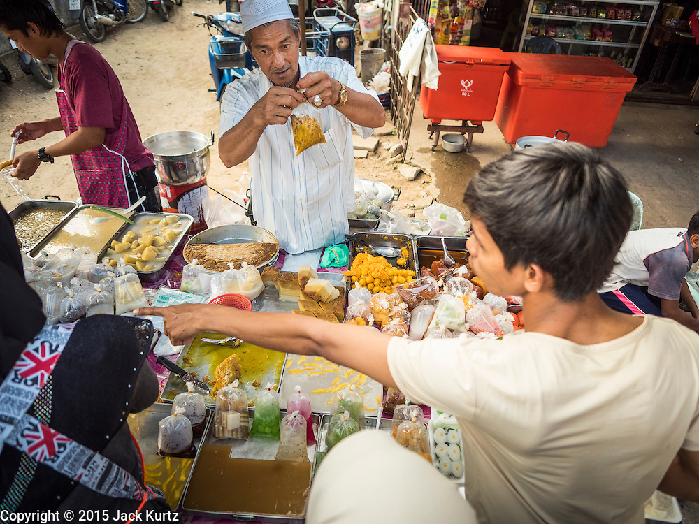 18 JUNE 2015 - PATTANI, PATTANI, THAILAND:   A dessert vendor in the Pattani Ramadan Bazaar, a large street food market that is only open during Ramadan. People come to the street food market late in the day to buy meals for the evening Iftar meal, which breaks the day long fast. Ramadan is the ninth month of the Islamic calendar, and is observed by Muslims worldwide as a month of fasting to commemorate the first revelation of the Quran to Muhammad according to Islamic belief. This annual observance is regarded as one of the Five Pillars of Islam. Islam is the second largest religion in Thailand. Pattani, along with Narathiwat and Yala provinces, all on the Malaysian border, have a Muslim majority.       PHOTO BY JACK KURTZ
