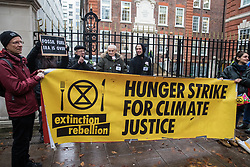 London, UK. 6 December, 2019. Climate change activists from Extinction Rebellion stand outside the Conservative party headquarters on the 19th day of a Global Hunger Strike for Climate Justice intended to apply pressure on political parties to place the climate and ecological emergency at the centre of their general election campaigning.