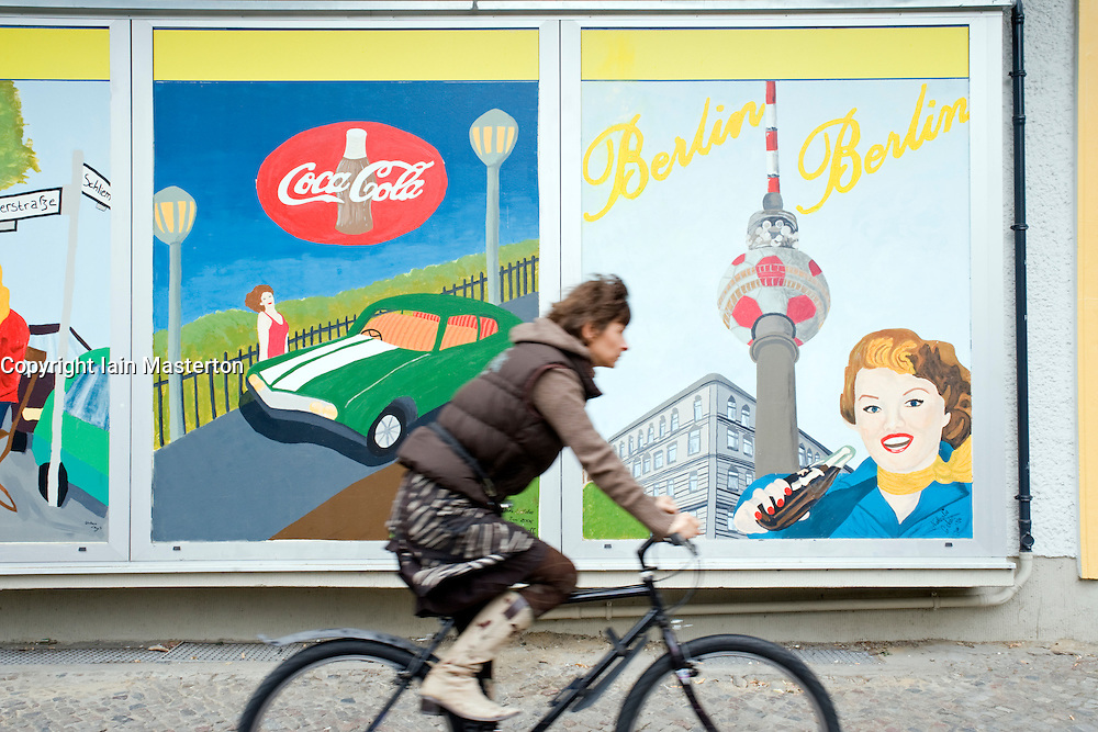 Woman cycles past painted mural on wall in Prenzlauer Berg in Berlin 2008