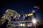 Egyptian protesters in Tahrir Square, Cairo, stand atop a burned out truck and wave flags to celebrate the news of President Hosni Mubarak's resignation following nineteen days of protests.