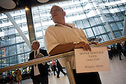 "From a low angle, we see a greeting driver from Dover Heritage Taxis who awaits his passenger to arrive off a flight from Turkey. In the hectic international arrivals concourse of Heathrow Airport's Terminal 5, the man holds up a name board to attract the attention of the man who is a member of a cruise ship's crew that is due to sail from the sea port of Dover. From writer Alain de Botton's book project ""A Week at the Airport: A Heathrow Diary"" (2009)."