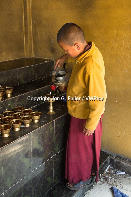 A young Buddhist monk prepares butter lamps at the Punakha Stupa in Punakha, Bhutan.