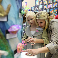 Adam Robison | BUY AT PHOTOS.DJOURNAL.COM<br /> Kristi Bounds looks at art work with her daughter Madelyne, a third grader at Mooreville Elementary School during the Lee County School's Art Show at the Gum Tree Museum of Art Friday afternoon in Tupelo.