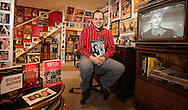 "John DiLeo of Milford, Pa., holds one of the four books he's published on movies while sitting in in his basement, which is filled with film memorabilia. A scene from ""Bachelor Mother"" with Ginger Rogers is on the television screen.  His other three books are on the table at left."