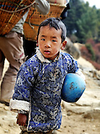 Nepal, Himalayas. Portrait of a Sherpa boy carrying a ball.