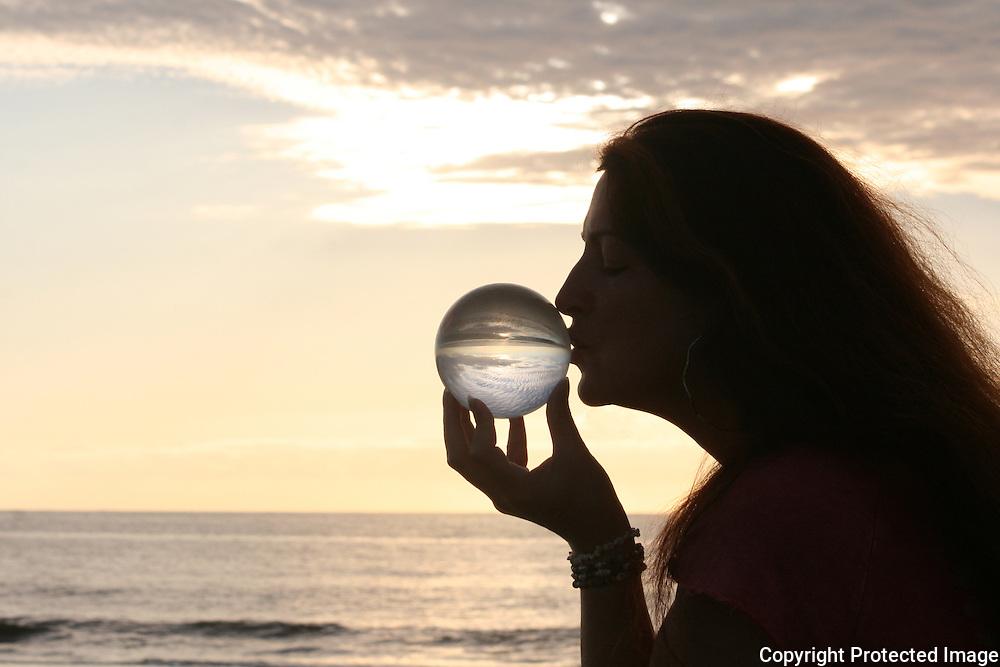 Red head woman kissing crystal ball on Jekyll Island Beach