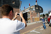 Tourists are taking part to an organised tour and taking pictures of the buildings in the BedZED housing complex on Thursday, Sep. 6, 2007, in London, UK. BedZED or the Beddington Zero Energy Development, is an environmentally-friendly housing development near Wallington, England in the London Borough of Sutton. It was designed by the architect Bill Dunster who was looking for a more sustainable way of building housing in urban areas in partnership between the BioRegional Development Group and the Peabody Trust. There are 82 houses, 17 apartments and 1,405 square meters of work space were built between 2000. The project was shortlisted for the Stirling Prize in 2003. The project is designed to use only energy from renewable source generated on site. In addition to 777 square meters of solar panels, tree waste is used for heating and electricity. The houses face south to take advantage of solar gain, are triple glazed and have high thermal insulation while most rain water is collected and reused. Appliances are chosen to be water efficient and use recycled water wherever possible. Low impact building materials were selected from renewable or recycled sources and were all originating within a 35 mile radius of the site to minimize the energy required for transportation. Also, refuse collection facilities are designed to support recycling and the site encourage eco-friendly transport: electric and LPG cars have priority over petrol/diesel cars, and electricity is provided by parking spaces appositely built for charging electric cars.