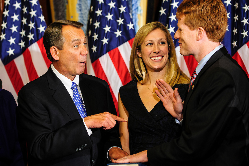 "Rep. John Boehner (R-OH) jokes with Rep. Joe Kennedy III (D-MA) as they participate in a mock swearing-in ceremony at the U.S. Capitol in Washington, District of Columbia, U.S., on Thursday, Jan. 3, 2013. The 133th Congress begins Thursday with the swearing in of newly elected Members of Congress and the election of the Speaker of the House of Representatives. New Members are afforded a ""photo opportunity"" with the Speaker following the official swearing-in ceremony. Kenndy's wife, Lauren Anne Birchfield, holds the Bible. Photographer: Pete Marovich/Bloomberg"