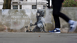 "© Licensed to London News Pictures. 27/04/2019. LONDON, UK.  A person walks by an artwork which has appeared on a wall at Marble Arch following ten days of protests in London by Extinction Rebellion, a group demanding that governments take action to tackle climate change.  Now covered in a protective plastic cover, the artwork has been attributed to the celebrated street artist Banksy and depicts an image of a plant and a girl holding a gardening tool with the Extinction Rebellion logo on it next to the text ""From this moment despair ends and tactics begin"".  Photo credit: Stephen Chung/LNP"