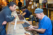 Shopper chats to roller at work on hand-rolled cigars of long leaf tobacco in cigar factory, Decatur Street, New Orleans, USA