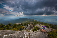 Female trail runner ascends a rocky ridge along the spine of the Green Mountains in Vermont as a storm closes in.