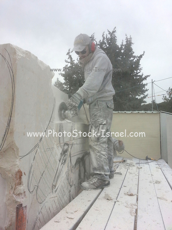 Sculpturing in Stone. Artist forming a large limestone with a power tool Photographed in Maalot, Israel