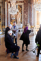 Elderly French tourists sit on portable stools while listening to a tour guide in the Hall of Mirrors in the Chateau Versaille, Paris, France