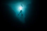 Dive buddies in silhouette during a dive at Spooky Channel, Roatan, Honduras.