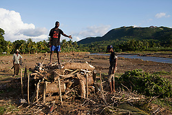 Three men gather fallen trees to make charcoal in Quartier Couzen, a small community southwest of Port au Prince.  The entire empty field behind them was filled with fruit trees, like mango and plantains, until the Cormier river flooded the area during Hurricane Sandy. Hurricane Sandy brought heavy flooding to the region , destroyed crops and livestock and will seriously hinder farmers' abilities to grow food in the future.