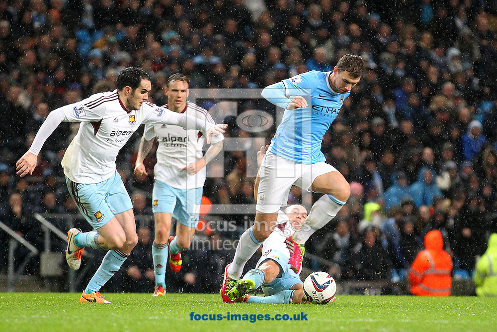 Picture by Paul Chesterton/Focus Images Ltd +44 7904 640267<br /> 08/01/2014<br /> Edin Džeko of Man City is tackled by Mark Noble of West Ham during the Capital One Cup Semi Final 1st Leg match at the Etihad Stadium, Manchester.