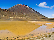 A sulfurous yellow pond lies beneath Mount Ngauruhoe (2291 metres or 7516 feet elevation), which last erupted in 1975 in Tongariro National Park, North Island, New Zealand. In 1990 and 1993, UNESCO honored Tongariro National Park as a World Heritage Area and Cultural Landscape.