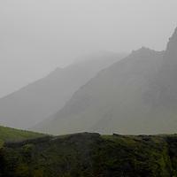 Layers of misty mountains beyond dark ridge.