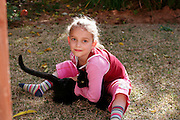 A young girl of 4 years of age and her pet black cat