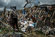 LACADONIE, HAITI - OCTOBER 10, 2016:  Lucienne Civil, 50, and her children work to clean up and salvage what is left of their home, that was destroyed by Hurricane Matthew.  The Civil family joined hundreds of other villagers and lived in a nearby cave for four days and nights, huddled in its womb before emerging, frightened the storm might return. They slept on a floor of stacked boulders near the cave's mouth, lighting small fires for light and warmth.  When they emerged to rebuild their village, they salvaged enough to shield them from the sun, a few corroded sheets of zinc and wooden beams. But when it rains they return to the cave - their shack is unable to keep the water out.  And despite the odor and humidity, the unforgiving crags and its depthless dark, they are thankful.  They now consider the cave a holy place, their only sanctuary left after the storm.