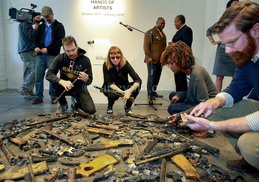 16 April 2014. Jonathan Ferrara Gallery, New Orleans, Louisiana. <br /> L/R; Artists Dan Tague (blue shirt) , Debora Luster, Katrina Andry and Adam Mysock  at the Jonathan Ferrara Gallery to announce the 'Guns In The Hands Of Artists' project where artists take parts from 190 destroyed weapons acquired by the New Orleans Police department through a buy-back program and convert them into art.  <br /> Photo; Charlie Varley/varleypix.com