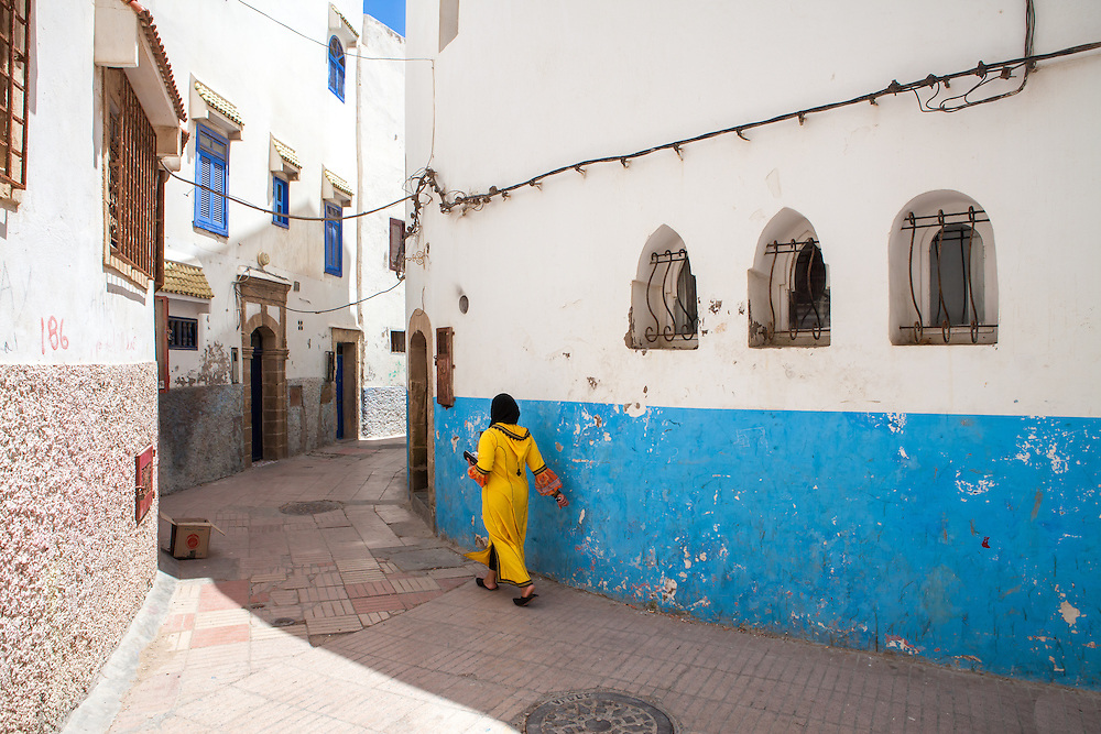 Young veiled muslim woman, dressed in a traditional yellow djellaba, on the streets of Essaouira, western Morocco.<br />