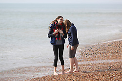 © Licensed to London News Pictures. 18/03/2015. Brighton, UK. Members of the public enjoy their lunch break sunbathing on Brighton Beach today, Wednesday 18th March 2015. Photo credit : Hugo Michiels/LNP