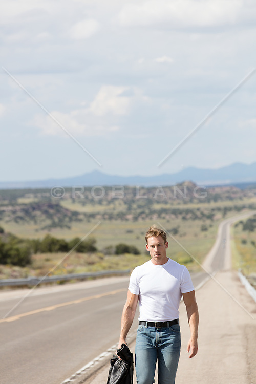 handsome man walking on a long road in New Mexico