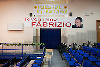 "Rosarno, Italy - 31 August, 2012: A banner in the highschool says ""We want Fabrizio back"", referring to Fabrizio Pioli, a 38 years old man who was killed in February 2012 and whose body is still missing in  Rosano, Italy, a mafia stronghold on August 31, 2012. Fabrizio Pioli was apparently killed by the family of Simona Napoli, the married woman who Fabrizio had an affair with and whose father is a fugitive mafia boss.<br /> <br /> Rosarno is an agricultural area best known for the violent race riots that erupted here in January 2010. and for being a hotbed of the 'Ndrangheta, a Mafia-type criminal organisation based in Calabria. The local 'Ndrangheta dominates the fruit and vegetable businesses in the area, according to Francesco Forgione, a former head of Italy's parliamentary Antimafia Commission. In December 2008, the entire town council was dissolved on orders from the central government and replaced by a prefectoral commissioner because it had been infiltrated by 'Ndrangheta members and their known associates.<br /> <br /> Calabria is one of the poorest Italian regions which suffers from lack of basic services (hospitals without proper equipment, irregular electricity and water), the product of disparate political interests vying for power. The region is dominated by the 'Ndrangheta (pronounced en-Drang-get-A), which authorities say is the most powerful in Italy because it is the welthiest and best organized.<br /> <br /> The region today has nearly 20 percent unemployment, 40 percent youth unemployment and among the lowest female unemployment and broadband Internet levels in Italy. Business suffer since poor infrastructure drives up transport costs.<br /> <br /> Last summer the European Union's anti-fraud office demanded that Italy redirect 380 million euros in structural funding away from the A3 Salerno - Reggio Calabria highway after finding widespread evidence of corruption in the bidding processes."