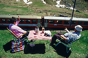 Trainspotters greet the Glacier Express at Oberalppass while having a picknick.