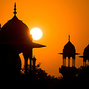 The guard towers of Agra's Red Fort are silhouetted against the setting sun in Agra, Uttar Pradesh, India.
