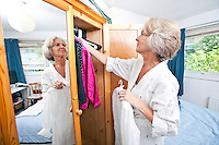 Senior woman selecting dress from closet at home