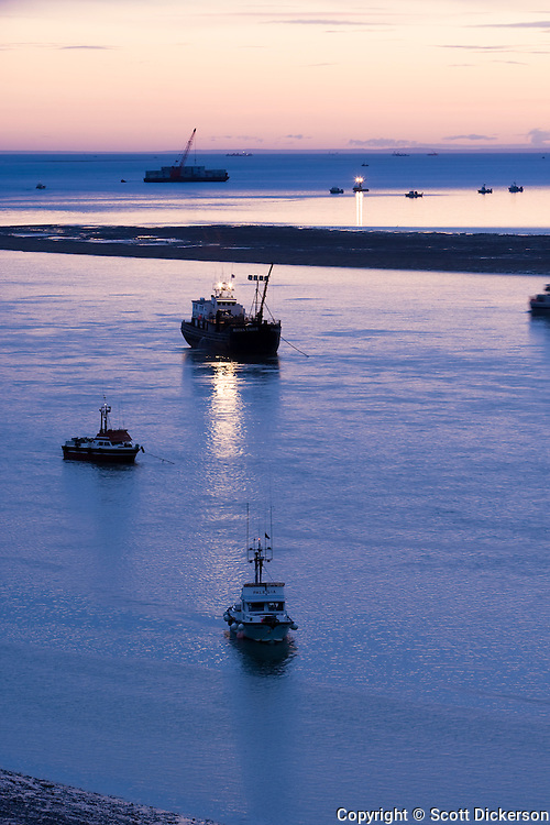 Commercial salmon fishing boats rest at anchor in the Naknek River after sunset in Bristol Bay, Alaska.