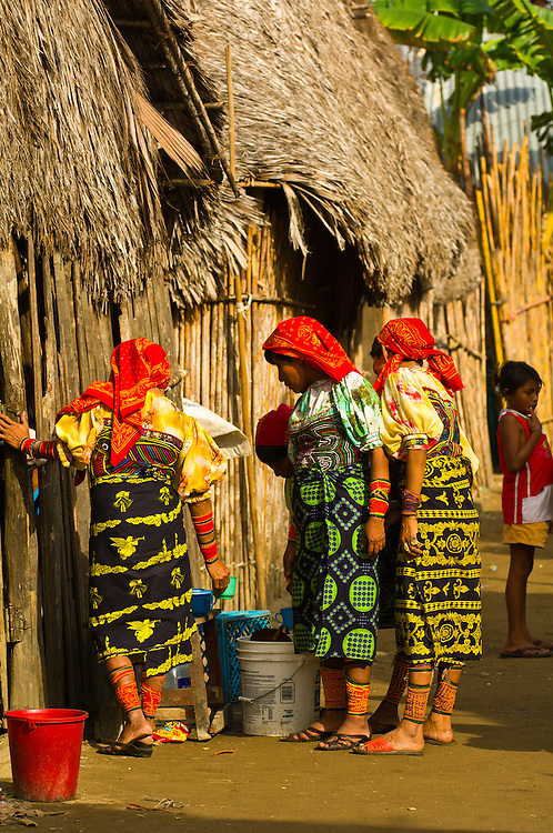 Kuna Indian women in native costume (with mola embrodery blouse) fetching water in the village on Crab Island (Carti Sugdup), San Blas Islands (Kuna Yala), Caribbean Sea, Panama